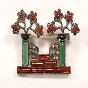Brooch showing a symmetrical composition of two stylized trees atop three tiered steps