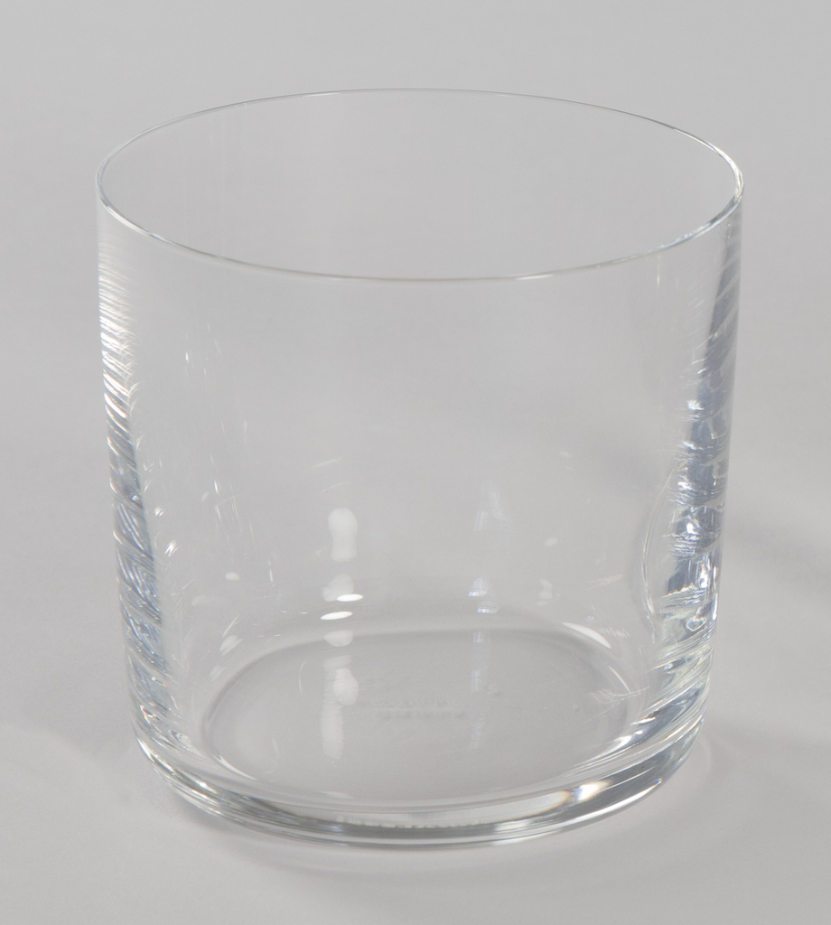 Water glass of crystalline glass with curved edges at base and straight sides.
