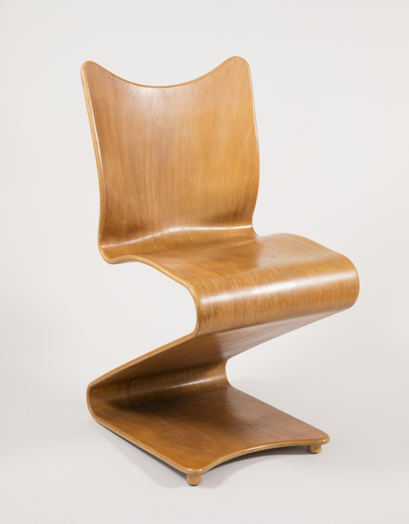 Cantilevered one-piece ribbon-like form of natural brown laminated plywood, the front of base and top of back with arc-shaped edges; sides of seat bent slightly upwards; front feet slightly raised.