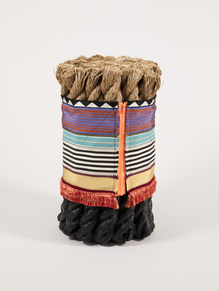 Narrow, cylindrical form composed of upright sections of thick coarse rope, coated in black polyurethane at the bottom, encircled by a zippered panel of stitched bands of colorful upholstery trimmings in gemetric patterns.