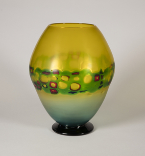 Transparent yellow to light blue glass decorated with an irregular stripe in transparent green glass embedded with murrine and foot in transparent blue glass.