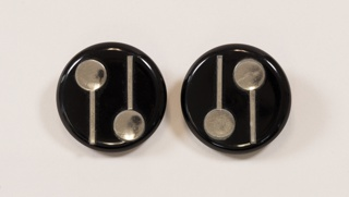Circular clip-on earrings in molded plastic with metallic geometric decoration