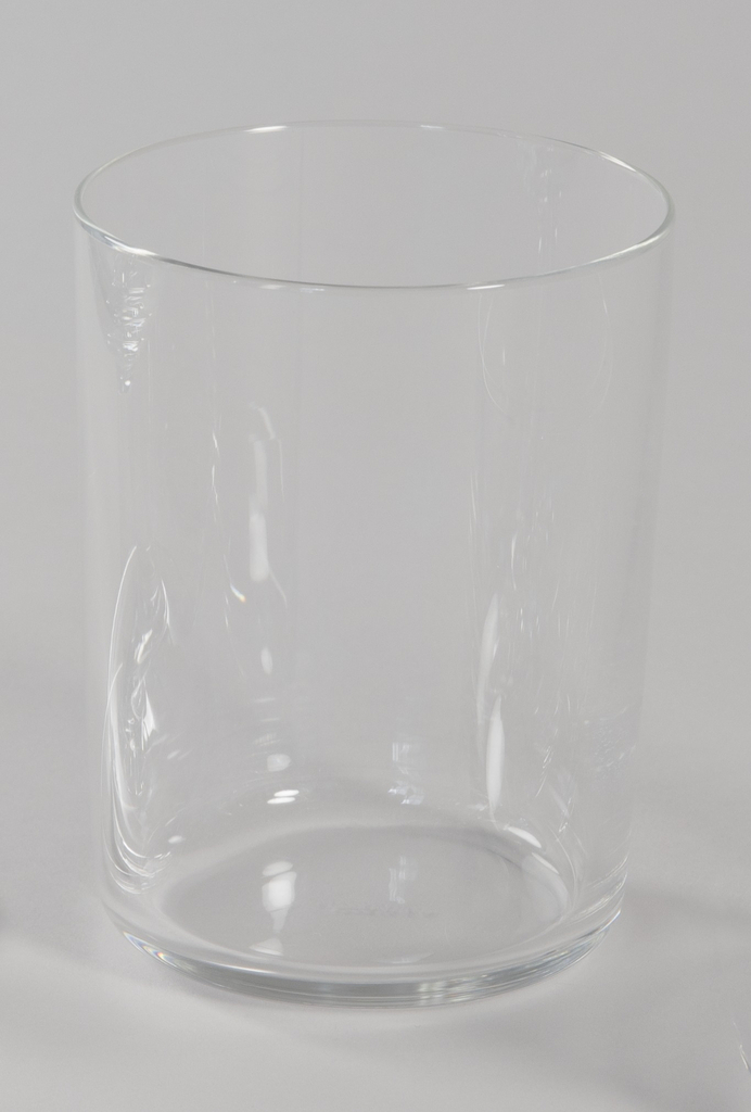 Stemless white wine glass of crystalline glass with curved edges at base and straight sides.