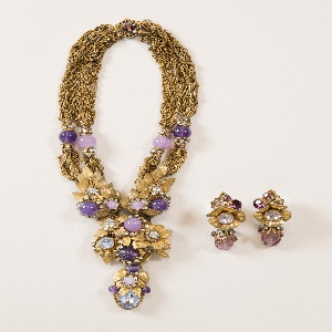 Necklace of gold chain terminating in a cluster of leaves and flowers centered with purple glass beads, semi-precious stones, and rhinestones.