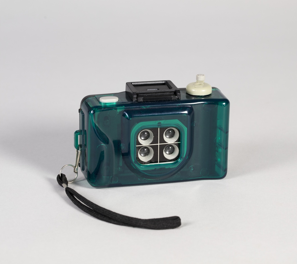 Molded transparent plastic camera equipped with four lenses in gridded configuration. Film rewinder, viewfinder, and shutter release at top; with carrying strap