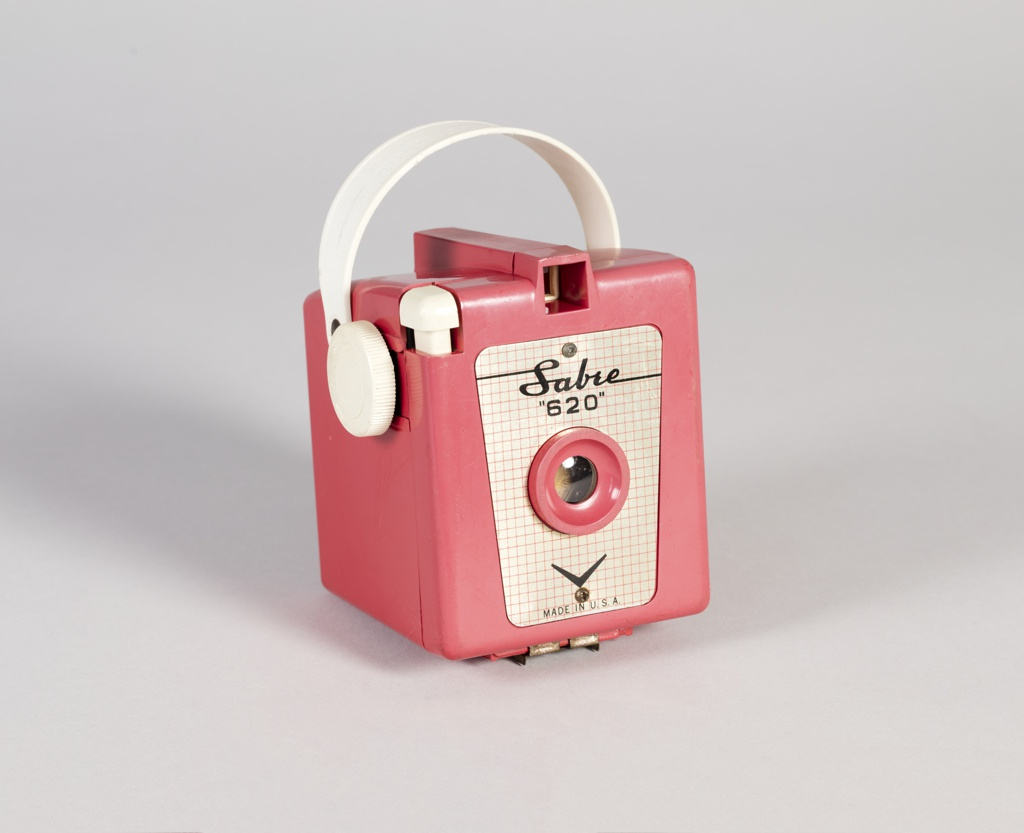 Box camera in pink molded plastic with carrying strap. Nameplate at front.
