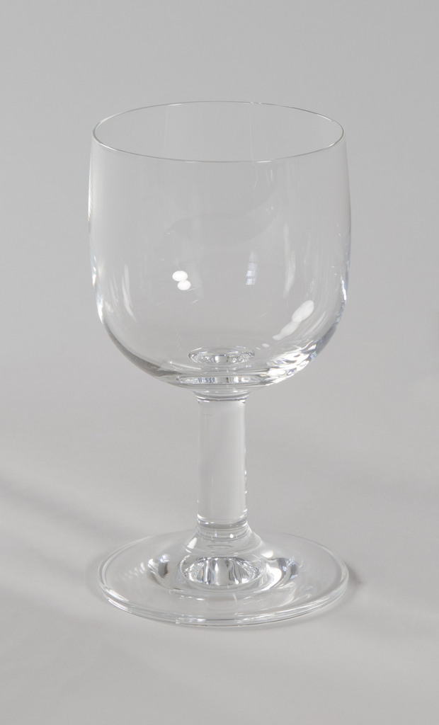 Clear glass goblet with slightly domed foot, thick cylindrical stem and bowl that tapers inward toward circular rim.