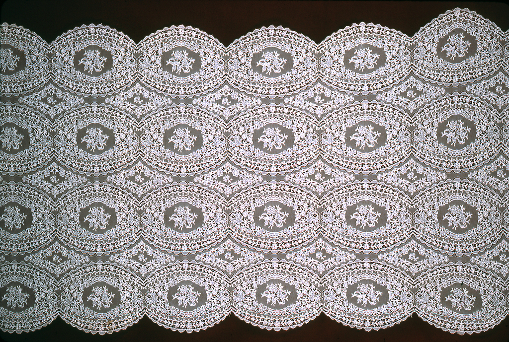 Lace band with an allover pattern of oval medallions enclosing a bouquet of flowers.