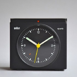 Square analogue alarm clock with fold-down cover for travel. White hour and minute hands and yellow second hand. Face displays Akzidenz Grotesk numerals. Raised alarm button with central red arrow at top. Ribbed body at back.
