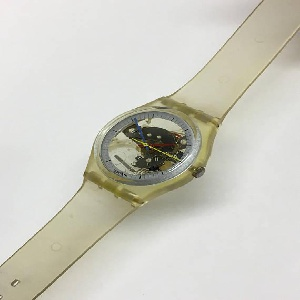 Watch with thin transparent plastic strap and flat round face; mechanism -- gears, springs, cans, and the battery -- exposed under a clear crystal; outer ring marked with hours and minutes; red hour hand, blue minute hand, and yellow second hand; swatch logo at bottom center of outer ring; dial to adjust time and date at center right.
