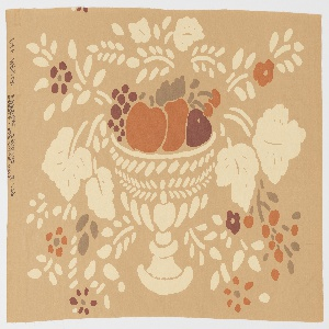 Taupe ground with a design of a pedestal dish holding an apple, pear and grapes with cascading flowers in off-white, dark red, tan and dark orange.