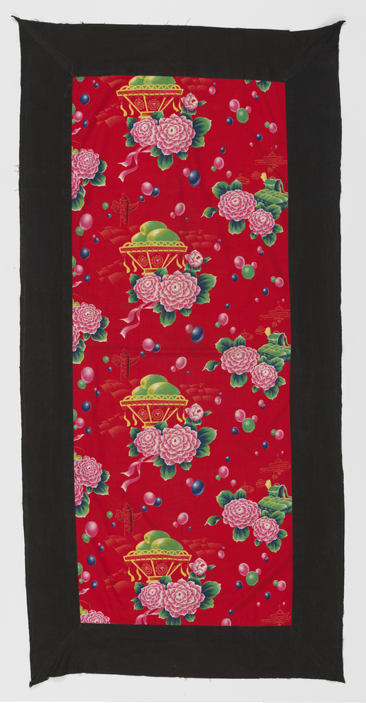 Quilt cover for a single bed. Bright red ground is printed with dahlias that resemble the paper flowers that were awarded to workers. In the center is a yellow basket with tassels swinging and with three yellow-green mangoes. Behind the basket is the imperial ornamental pillar (huabiao) which is a symbol of political authority that stands in front of Tiananmen Gate. To the left is a drum, cymbals and a musical instrument called an erhu. Behind that motif is a building in which the mango possibly was exhibited. On the right is a bedroll and satchel with the Highest Directive sticking out. Colored balloons float above.