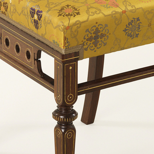 The back of inlaid open rectangular latticework surmounted by an incurved crest band inlaid with a rod with ribbons holding a banner, side stretchers separated with three circular voids, side supports, tapered legs and stretchers all with gilded incuse lines; the yellow Chinese silk upholstery fabric of the period but replaced.