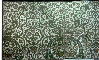 Similar wallhanging used in two rooms in Winterthur Museum, Delaware (1955). Has been folded under along top and cut to fit about a ceiling beam. Has been moth-eaten, and perforated with nail holes. Small stylized floral motif set within tracery, printed in green flock and orange pigment, on metallic gold color ground.