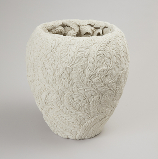A white vase shaped ceramic with a wide lip which tapers to a narrrow foot. Vase surface has a textured exterior with leaf pattern covering full exterior.