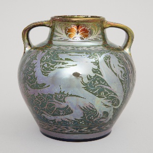 Two handled vase with a lusterware glaze, ornamented in resist copper-colored decoration. Vase decoration consists of two heraldic lions along with foliage and twining vines. In interior of vase, mechanism has been placed to turn it into a lamp, but it does not compromise the body of the vase.