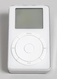 "Rectangular form; white front having rectangular read-out screen above circular scroll wheel with central button, and surrounded by circle made up of four raised, curved segments: the top segment with ""menu"", the remaining segments (starting at right, going clockwise) with symbols for forward, pause, and back. Back of silver-colored plastic with Apple logo and product information. Control switches and jacks on top."