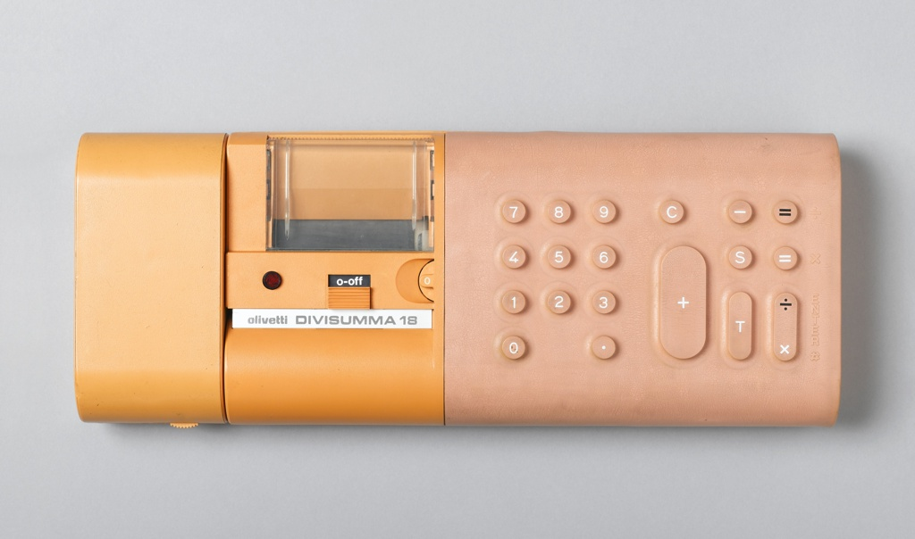 """Low, horizontal rectangular form with curved edges; left side: yellow, molded plastic housing for paper and print mechanism; right side: rectangular rubber keypad molded with circular and lozenge-shaped number and function keys. On front, imprinted: """"olivetti DIVISUMMA 18""""."""