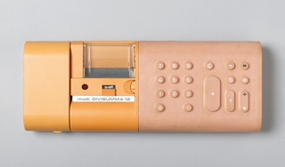 "Low, horizontal rectangular form with curved edges; left side: yellow, molded plastic housing for paper and print mechanism; right side: rectangular rubber keypad molded with circular and lozenge-shaped number and function keys. On front, imprinted: ""olivetti DIVISUMMA 18""."