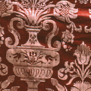 An offset repetition of an eared vase holding flowers in red and white. Both selvages present.