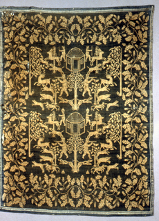White warp and blue weft form a reversible design with a checkerboard outer border. Broad inner border has a vine with oak leaves and acorns. Symmetrical design of two horizontal repeats of central octagonal building and tree flanked by hunters, some with spears and muskets along with dogs, deer and rabbits.