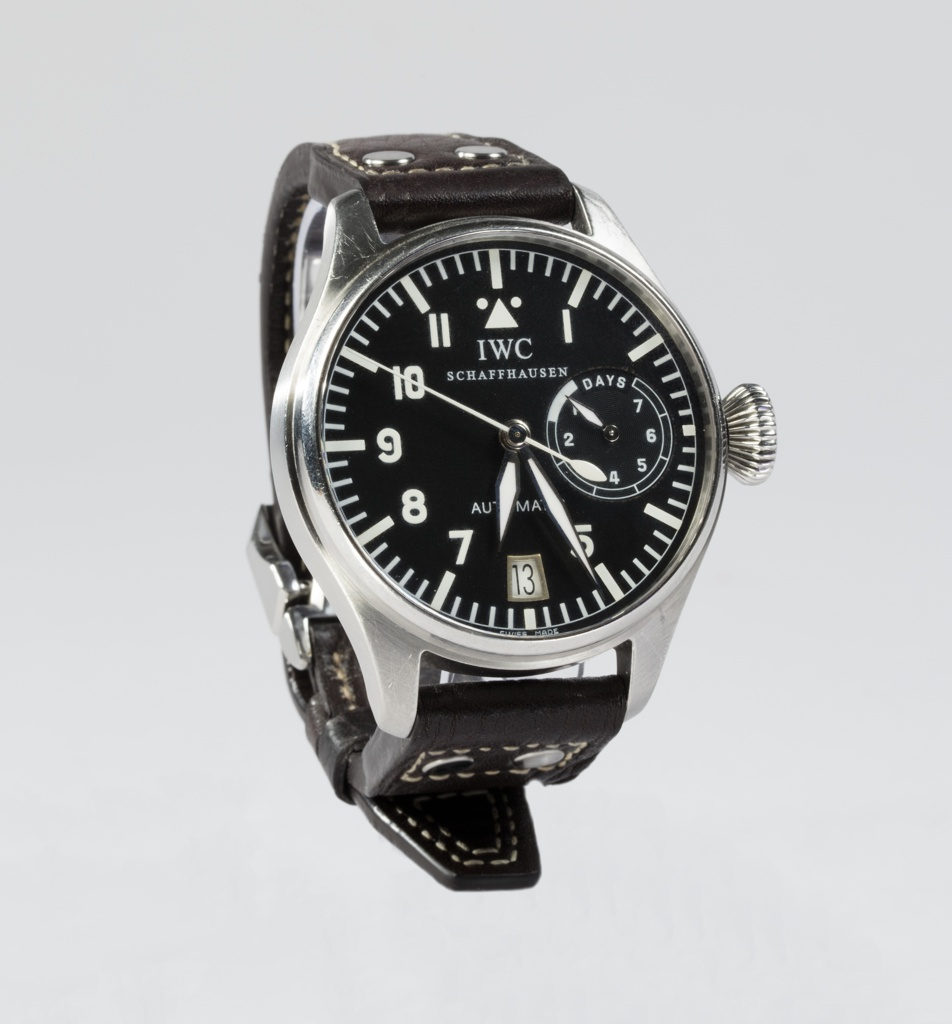 Analog wrist watch with 7-day movement reserve, date display at six o'clock, central seconds' display, conical crown, and leather band