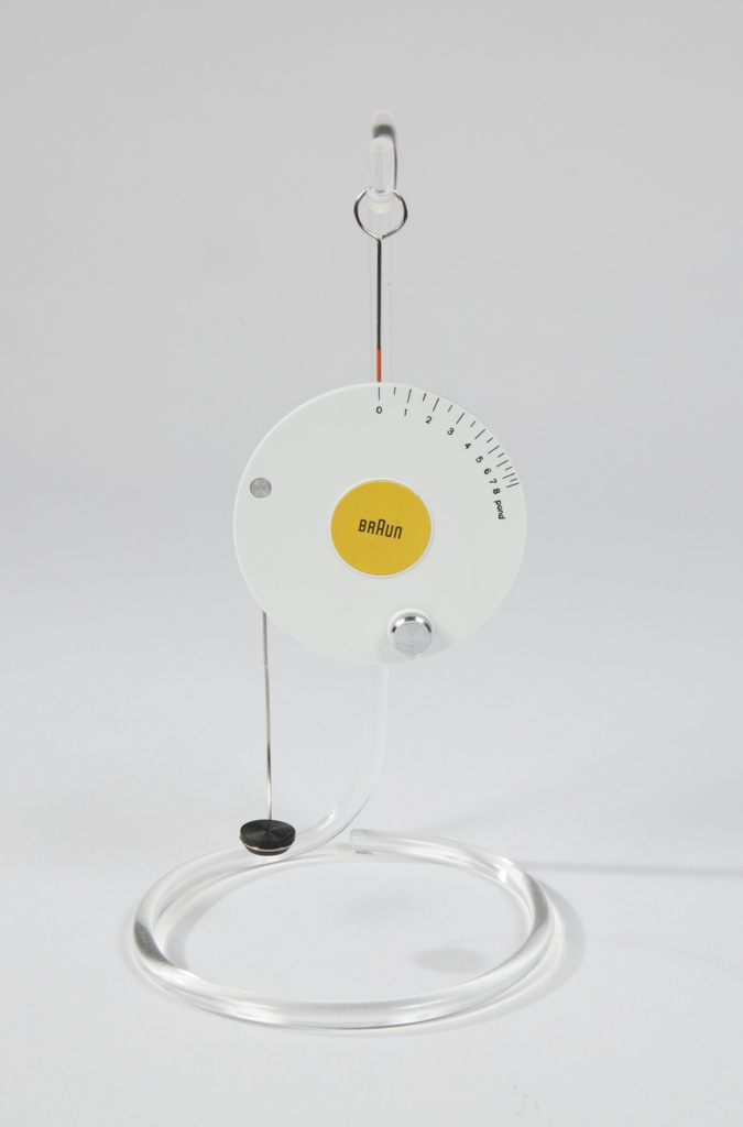 Circuar hanging scale; white outer circle with increments in ponds around outer edge; yellow center with Braun logo. Wire hook at top and wire arm with foam semi-circle end at bottom.
