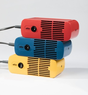 Red, blue and yellow hair dryers in rounded rectangular shape. Each has a front face of a bisected slotted grill. Two central rows of slits correspond to the placement of a black rocker switch. Braun logo appears at center left. With black cord.