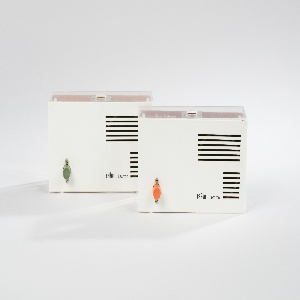 Two rectangular intercoms with off-white molded plastic front with vented grill and green or orange knob in bottom lefthand corner. Sides and backside of objects are constructed of clear Perspex, revealing the inner circuitry.