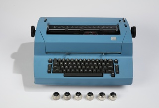 "Typewriter in bright blue housing with a boxy profile; black QWRTY keyboard and function keys; black plate IBM logo with ""Correcting Selectric II"" below in small silver square on top right ledge of body."