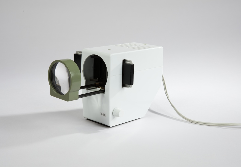 White plastic casing with a split line that lines up with the direction of the lens; viewing screen extends at side and lens, with green rim, extends for viewing; Braun logo on front face at bottom right corner; electrical cord and plug at back.