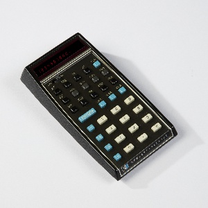 Rectangular calculator with sloped screen; raised keyboard with white, turquoise, and black keys, when lit, screen shows red LED numbers; power switch at top and Hewlett-Packard logo along bottom edge of plastic casing.