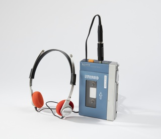 Blue molded plastic rectangular body with aluminum strip on right side. Two earphone jacks at top. Translucent window on front face/hinged cover shows cassette inside. SONY logo across top. Earphones in black and silver plastic with circular orange foam earpieces.