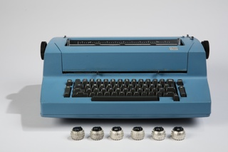 """Typewriter in bright blue housing with a boxy profile; black QWRTY keyboard and function keys; black plate IBM logo with """"Correcting Selectric II"""" below in small silver square on top right ledge of body."""