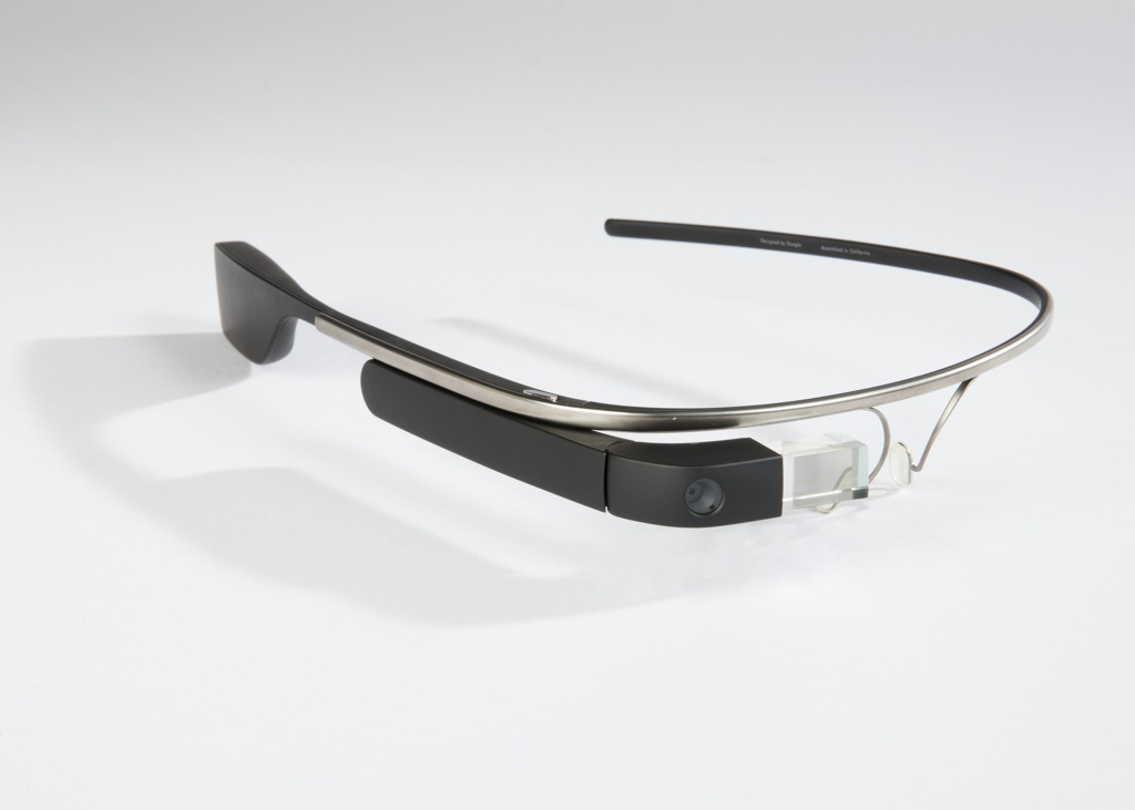 Eyeglass-like titanium frame with adjustable nose pieces; the left arm a simple band, the right arm with clip-on unit housing a 5-megapixel camera, touch-sensitive control panel, computer and display-projecting prism that sits in front of the wearer's eye; battery and bone-conduction speaker at back of right arm, that sits just behind wearer's ear.