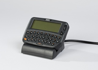 Rectangular gray body with rounded corners; QWERTY keyboard below rectangular digital read-out screen. RIM logo at top center. Sits in rectangular gray charging cradle.