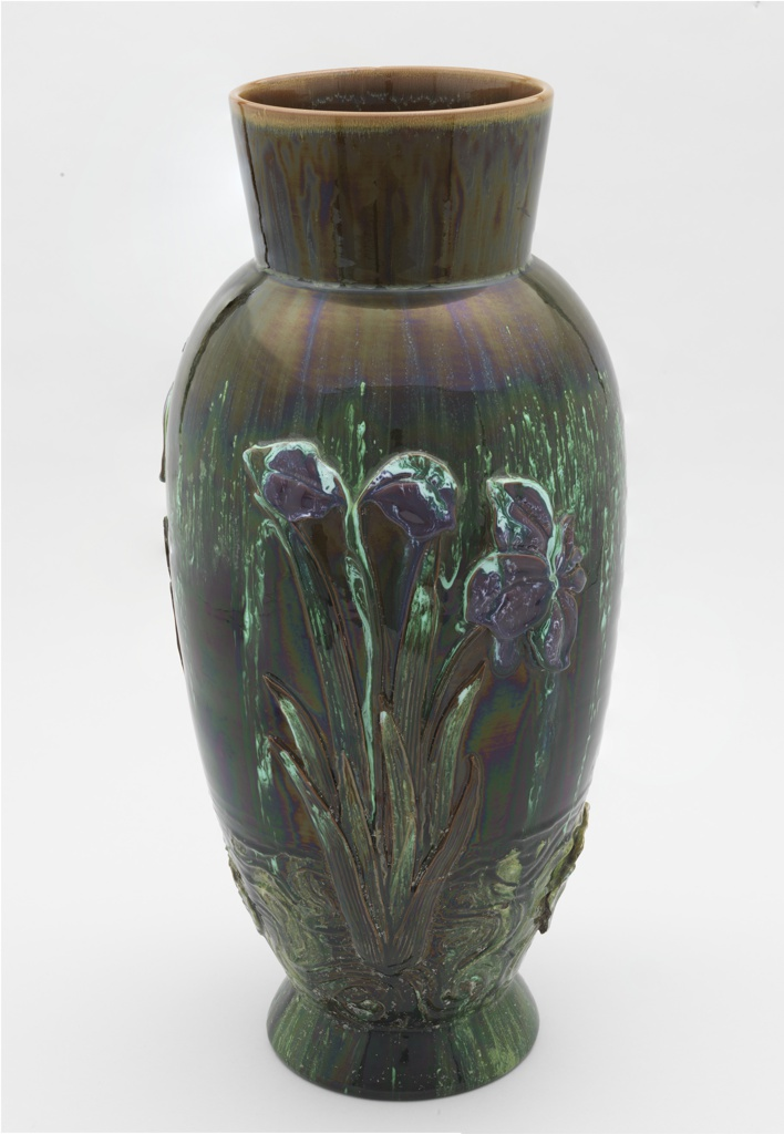 "Red earthenware body. Elongated ovoid shape, flared foot, flared ""collar"" neck. Body applied with molded iris with purple glaze, and white water lilies, both with foliage emerging from stylized water lines. Body glazed in striated brown, green and white, with surface iridescence. Interior glazed."