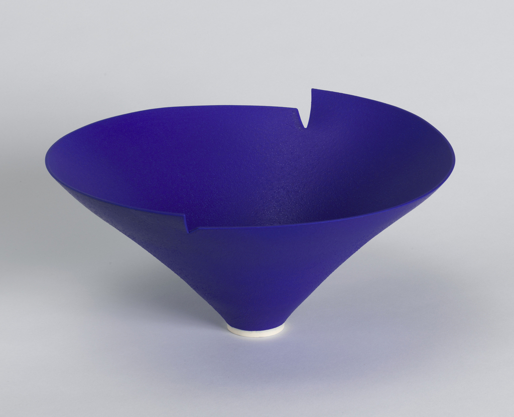Bright blue ceramic bowl of inverted conical form with notched rim of opposing heights; narrow circular foot in white.