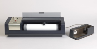 An early fax machine. A large rectangular machine with a front opening printing area. Connected via cord to an acoustic coupler that housed the phone receiver.