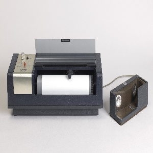 A large rectangular machine with a front opening printing area. Connected via cord to an acoustic coupler that housed the phone receiver.