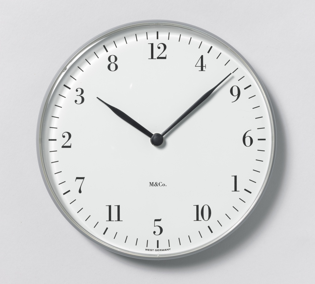 Analog wall clock with two-hand movement. Numbers appear around dial in random order.