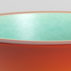 Bowl of inverted conical form, the thick outer shell of cast, orange polyester resin bonded to a white porcelain liner, its inner surface glazed turquoise; flat flat rim showing layers, flat circular base.