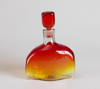 The flattened, undulating body incorporating multi-fired tangerine color above a lemon yellow, with uneven applied clear glass shoulders and neck, below a red stopper.