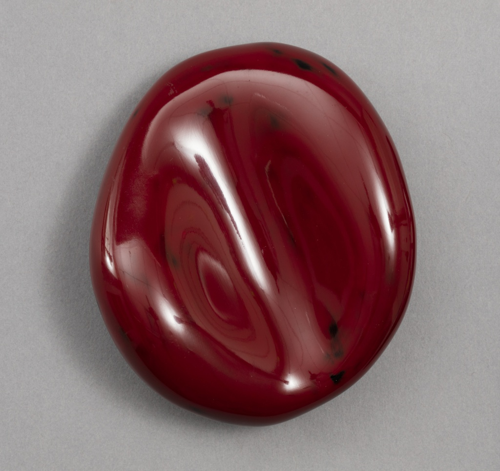 Roughly ovoid form with irregular surface in black-specked, lustrous cinnabar red.
