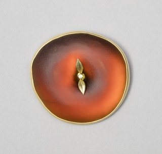 "Roughly circular red glass form resembling an apple seen from above, with gold edge and two gold leaves and ""stem"" in center."