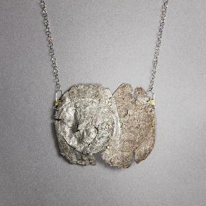 Crushed, flattened soda cans with applied  zircons on metal chain.