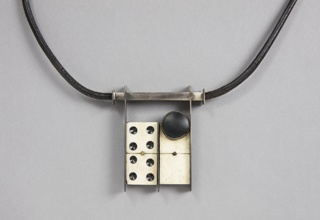 Necklace composed of leather cord with focal point of silver framed, ivory dominos. Two decorative discs ornament the necklace. One is ivory, attached as a clasp, the other is black and rests on the blank domino. Both discs are bezel set. The focal piece is suspended  from a squared silver tube. Dominos are set on a black substrate and are framed by thin silver bars.