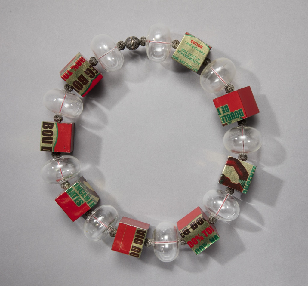 Clear glass orbs alternating with beads and steel cubes with brightly colored graphics on surfaces; all strung on red thread.