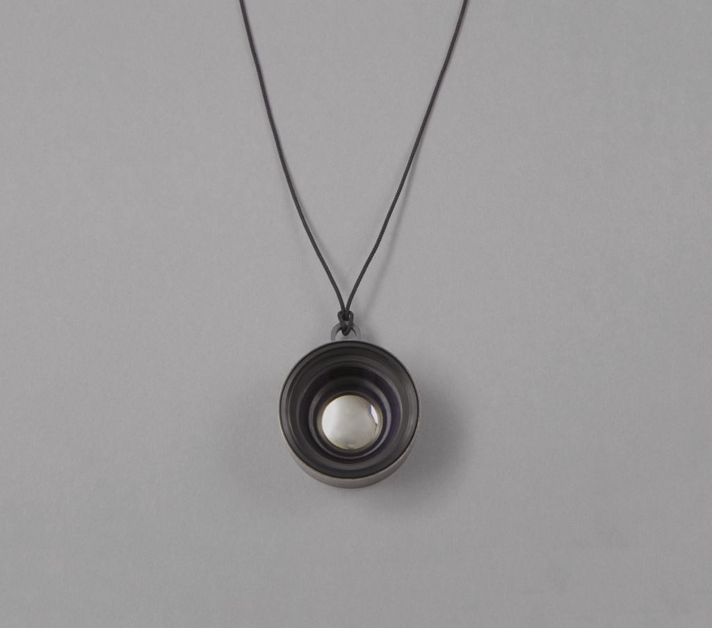 Lense as circular pendant hanging from long cord.