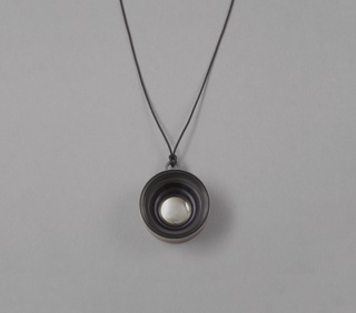 Lense as circular pendant hanging from long cord.